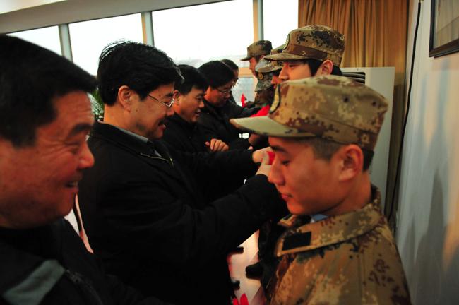 校领导为入伍同学配戴光荣大红花-我校欢送09年首批入伍同学